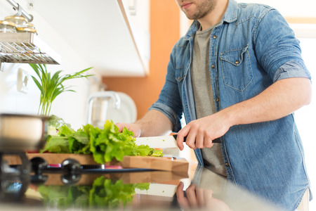 Man cooking and cutting veggies for lunch Imagens