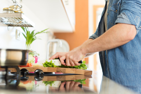 nutricion: Man cooking and cutting veggies for lunch Stock Photo