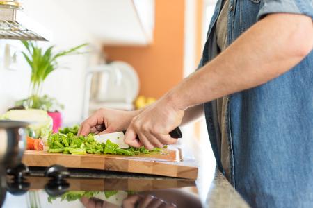 hombre cocinando: Hombre que cocina y cortar las verduras para el almuerzo