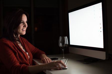 dependent: Woman in video call with a glass of wine on hand