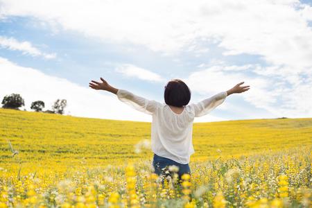 detras de: Volver la vista de una mujer en el campo amarillo Foto de archivo