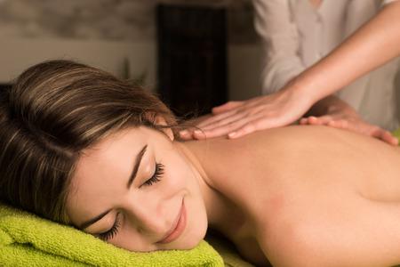 Junge Frau mit einer Rückenmassage im Wellnessbereich Standard-Bild - 39955875