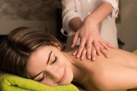 Young woman having a back massage at the spa photo