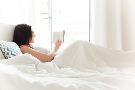 Woman reading book in bed during the morning