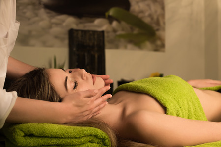 Woman doing face massage in spa clinic