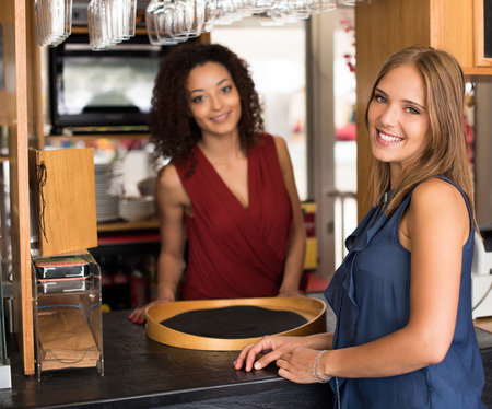 baristas: Couple of female baristas standing inside their coffee house