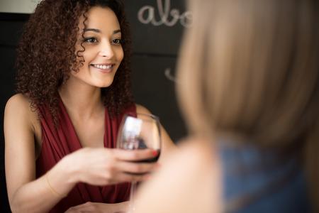 tomando vino: Amigos étnicos multi hablando y bebiendo en el bar