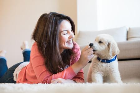 Vrouw liggend op de vloer met een puppy Stockfoto