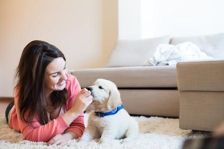 子犬と床に横たわる女