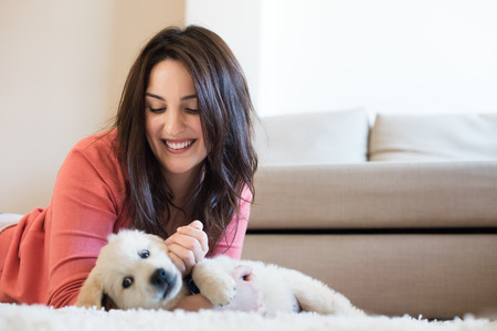 cute puppy: Woman lying on floor with a puppy Stock Photo