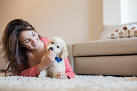 Woman lying on floor with a puppy Standard-Bild