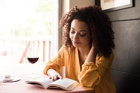 女性は、喫茶店で本を読んで