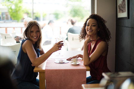Pretty women talking and having fun inside coffee shop photo