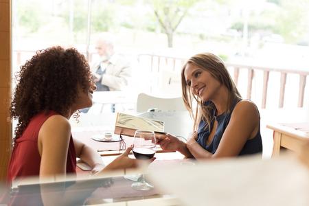 Pretty women talking and having fun inside coffee shop photo