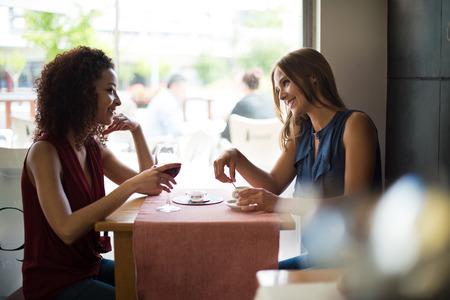 gente sentada: Mujeres bonitas que hablan y que se divierten en el interior de la cafeter�a