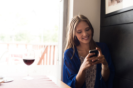 casual woman: Casual woman using smartphone at coffee shop Stock Photo