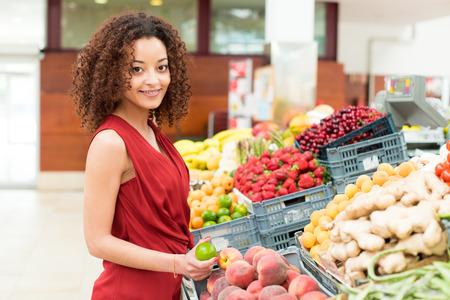 tiendas de comida: Mujer Afro compras verduras y frutas org�nicas Foto de archivo