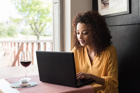 Casual woman using laptop at coffee shop Stock Photo