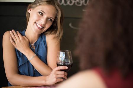 copa de vino: Amigos étnicos multi hablando y bebiendo en el bar