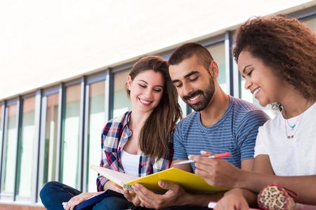 学生は大学キャンパスのノートを共有します。 写真素材