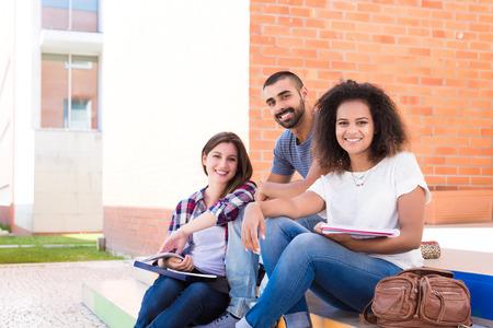 akademický: Skupina studentů sedí na schodech školní