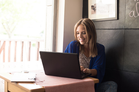 shop online: Casual woman using laptop at coffee shop Stock Photo