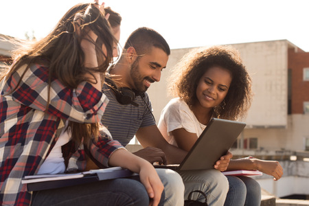 young student: Multi-Ethnic group of students with laptop in campus - Soft sunset Light Stock Photo
