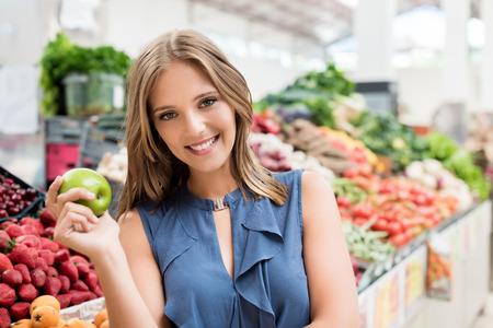 buying: Blonde woman shopping organic veggies and fruits
