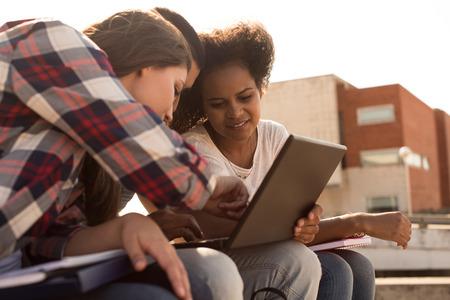 Multietnická skupina studentů s notebookem v areálu - Soft Light západ slunce Reklamní fotografie