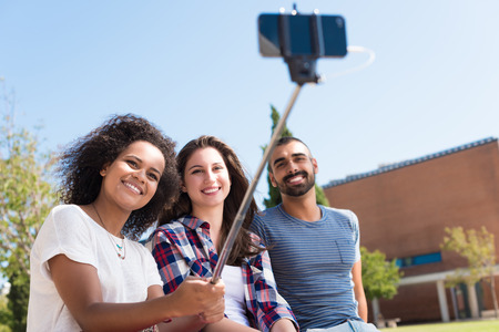 multiracial: Friends taking a photo with a selfie stick