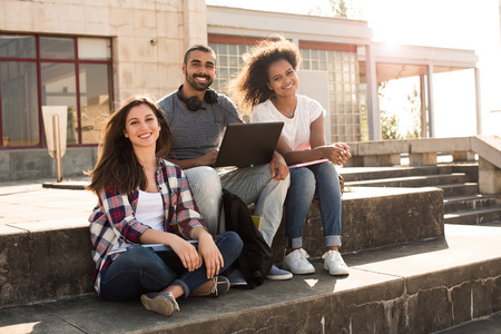 Multi-Ethnic group of students with laptop in campus - Soft sunset Light Stock Photo