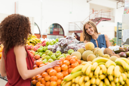 biologic: Multi-etchnic women trading organic veggies and fruits Stock Photo