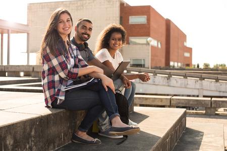 juventud: Grupo multiétnico de estudiantes con la computadora portátil en el campus - Luz Puesta del sol suave