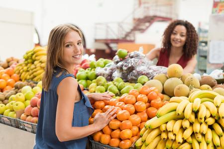 Multi-etchnic women trading organic veggies and fruits Archivio Fotografico