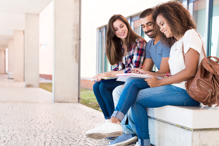 college campus: Students sharing notes in the university campus