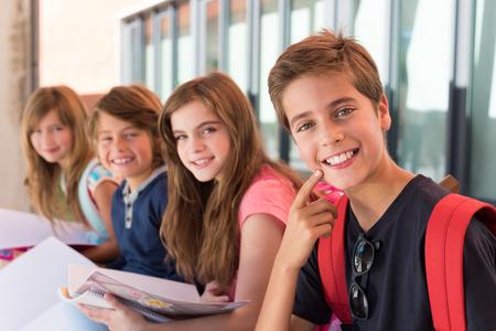 clases: Grupo de felices los niños pequeños escolares en la escuela