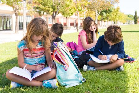 Groep kleine studenten zitten op het gras op school Stockfoto