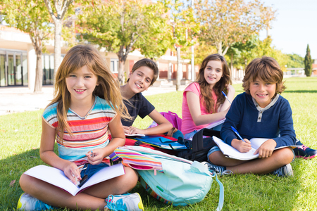 book bags: Group of little students sitting on the grass at school