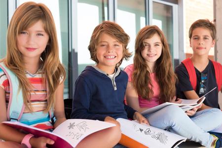 дети: Группа счастливых маленьких школьников в школе