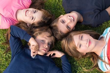 niños rubios: Grupo de niños que mienten en hierba Foto de archivo
