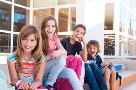 niño con mochila: Grupo de niños de la escuela que se sienta en las escaleras
