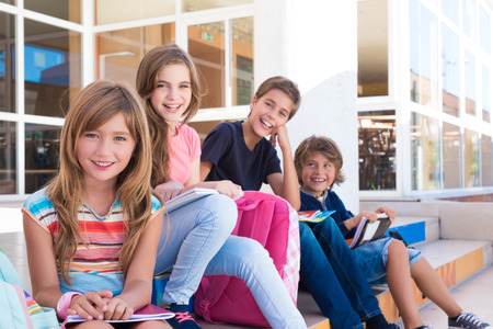 book bag: Group of school kids sitting on stairs