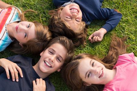 niñas jugando: Grupo de niños que mienten en hierba Foto de archivo
