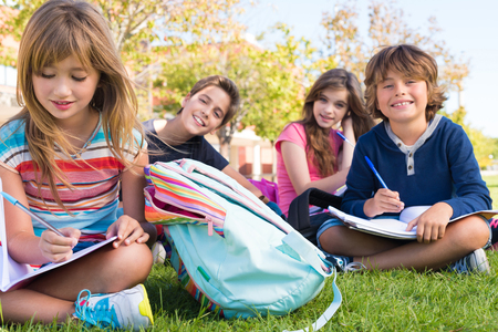 niños sonriendo: Pequeño grupo de estudiantes que se sientan en la hierba en la escuela Foto de archivo