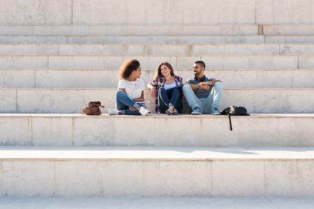 estudiantes universitarios: Grupo de estudiantes que se sientan en las escaleras de la escuela Foto de archivo