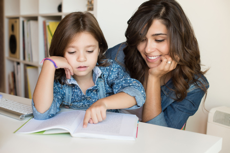 two parents: Mother helping her little child with homework