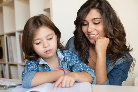 little: Mother helping her little child with homework