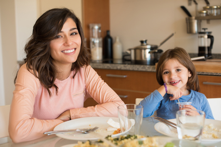 hispanic kids: Mother and daughter having lunch in the kitchen