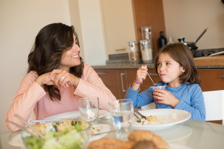 hispanic girl: Mother and daughter having lunch in the kitchen