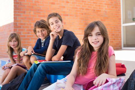 niño con mochila: Grupo de felices los niños pequeños escolares en la escuela